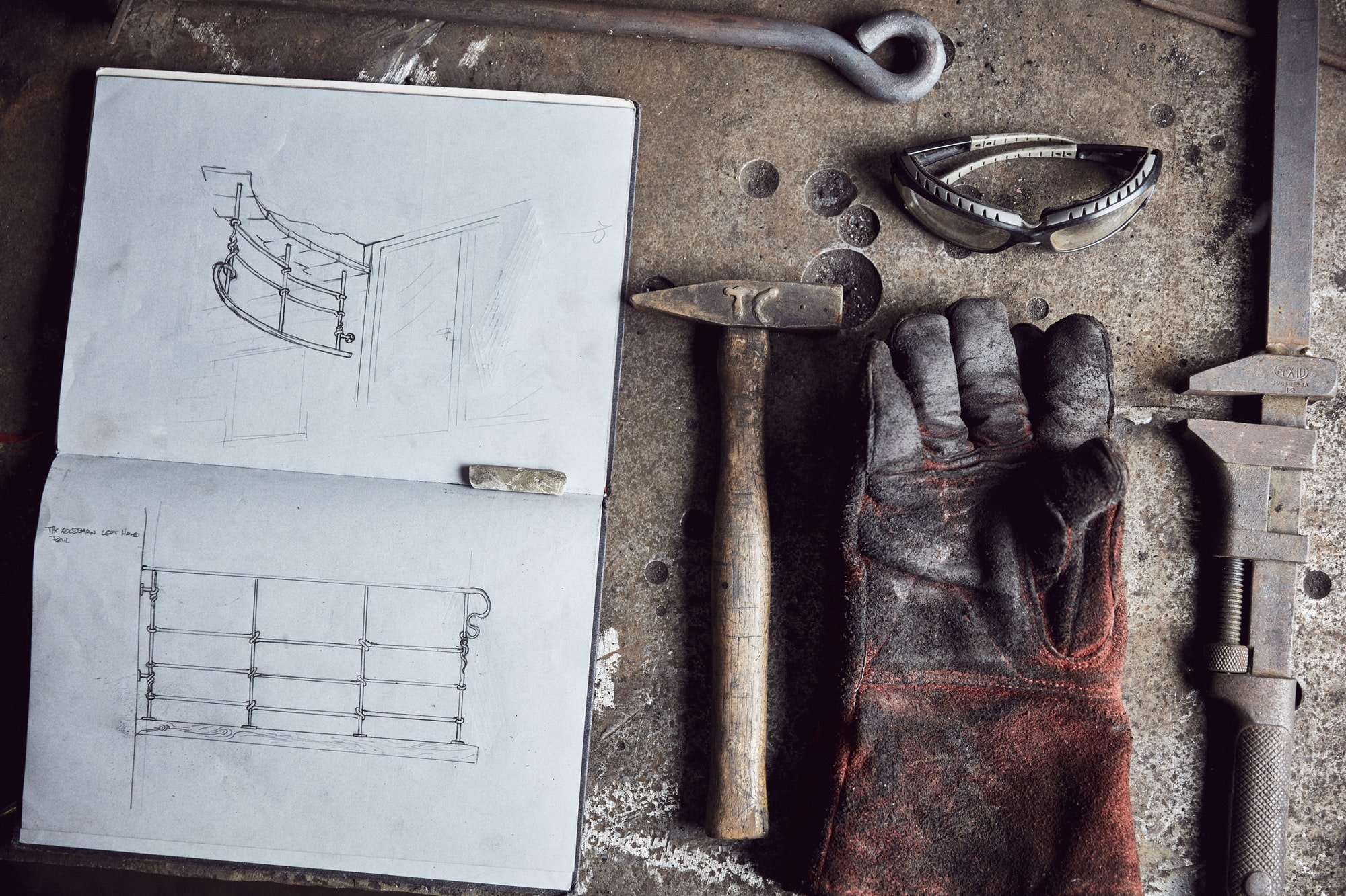 Artisan metalworker's tools, sketches in a notebook and a glove