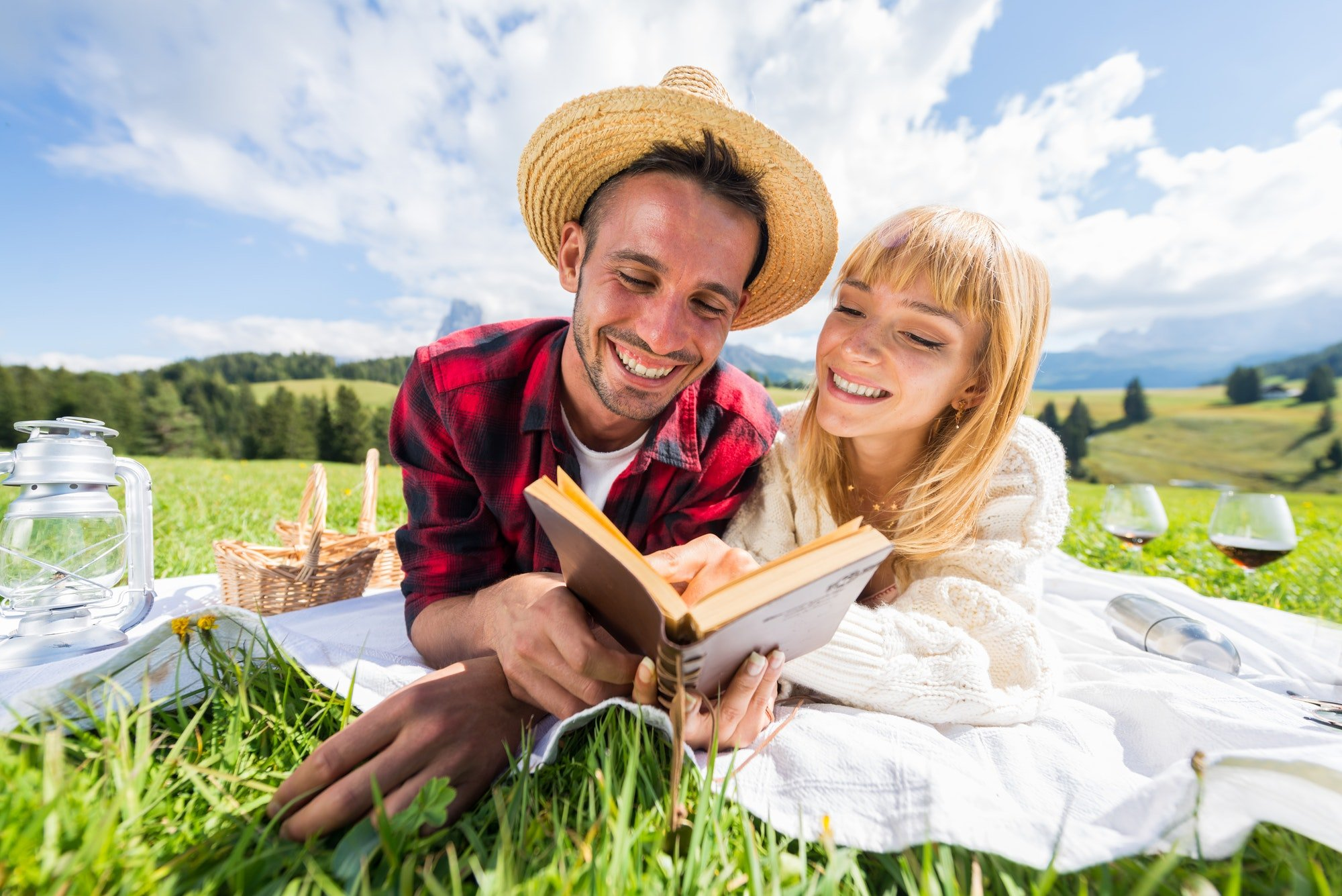Portrait of a young couple in love doing picnic visiting alps dolomities.